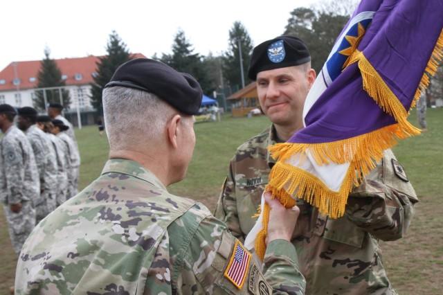 Brig. Gen. Arlan DeBlieck, commanding general of the 7th Mission Support Command, hands the unit colors to Col. John Novak, incoming commander of the 361st Civil Affairs Brigade during the brigade's change of command ceremony Sunday, April 3, 2016 at Daenner Kaserne in Kaiserslautern, Germany. (Photo by Lt. Col. Jefferson Wolfe, 7th Mission Support Command Public Affairs Officer)