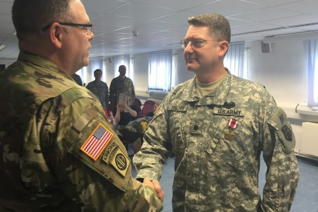 Lt. Col. Joel D. Fischer, outgoing commander of the 7th Intermediate Level Education Detachment, shakes hands with Col. Kevin M. Sanders, deputy commanding officer of the 7th Mission Support Command, Saturday, April 2, 2016 after the 7th ILE's change of command ceremony. (Photo by Chaplain Lt. Col. Brian Harki, 7th Mission Support Command)