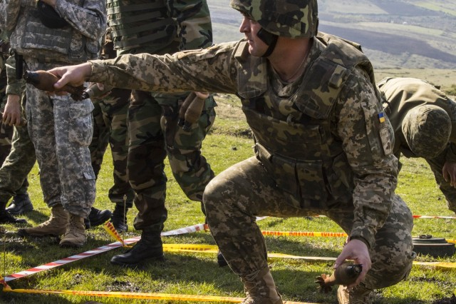 Members of a Ukraine explosive ordnance disposal team work together to move a pile of unexploded ordnance during a joint mine clearing operation April 4, at Orahovac Demolition Range in Kosovo. More than 60 UXO's, found throughout Kosovo, were disposed of during a joint mine clearing operation. The operation included EOD teams from the Kosovo Security Forces, Swiss, U.S., Moldovan and Ukraine armies.