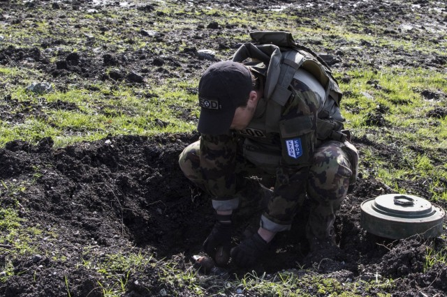 A member of the Swiss explosive ordnance disposal team places an unexploded ordnance into an individual pot, also referred to as pre dug hole in the ground, during a joint mine clearing operation, April 4, at Orahovac Demolition Range in Kosovo. More than 60 UXOs, found throughout Kosovo, were disposed of during a joint mine clearing operation. The operation included EOD teams from the Kosovo Security Forces, Swiss, U.S., Moldovan and Ukraine armies.