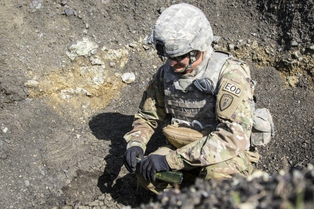 U.S. Army Sgt. Eric Wallace, an explosive ordnance disposal technician with the Multinational Battle Group-East, places C4 explosives onto a stack of unexploded ordnances April 4, at Orahovac Demolition Range. More than 60 UXOs, found throughout Kosovo, were disposed of during a joint mine clearing operation. The operation included EOD teams from the Kosovo Security Forces, Swiss, U.S., Moldovan and Ukraine armies.