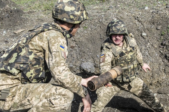 Members of a Ukraine explosive ordnance disposal team place unexploded ordnances into individual pots, or also referred to as pre dug holes in the ground, during a joint mine clearing operation, April 4, at Orahovac Demolition Range in Kosovo. More than 60 UXOs, found throughout Kosovo, were disposed of during a joint mine clearing operation. The operation included EOD teams from the Kosovo Security Forces, Swiss, U.S., Moldovan and Ukraine armies.