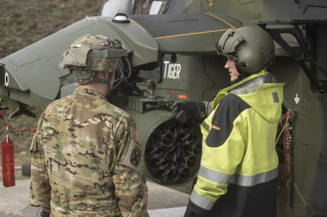A Soldier from 1st Battalion, 3rd Aviation Regiment, 12th Combat Aviation Brigade, discusses munitions procedures with a German Tiger helicopter safety officer at the forward arming and refueling point (FARP). The 1st Bn., 3rd Avn. Regt., recently completed their combined combat aerial gunnery from March 16-April 05, at the Grafenwoehr Training Area, Germany. (U.S. Army photo by Sgt. Thomas Mort, 12th CAB)