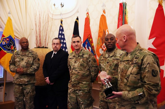 Maj. Gen. John B. Morrison Jr. (far right), commander of U.S. Army Network Technology Command, and Command Sgt. Maj. Stephfon Watson (far left), NETCOM senior enlisted advisor, present the award for 2015 NETCOM NEC of the Year to leaders from the 102nd Signal Battalion, 2nd Signal Brigade at an Orange Call event March 21, 2016 at the Community Activity Center on Clay Kaserne in Wiesbaden, Germany. From center left to center right: James Ellersick, 102nd Signal Battalion regional director; Lt. Col. Chris Keeshan, 102nd Signal Battalion commander; Command Sgt. Maj. Anthony Davis, 102nd Signal Battalion senior enlisted advisor.