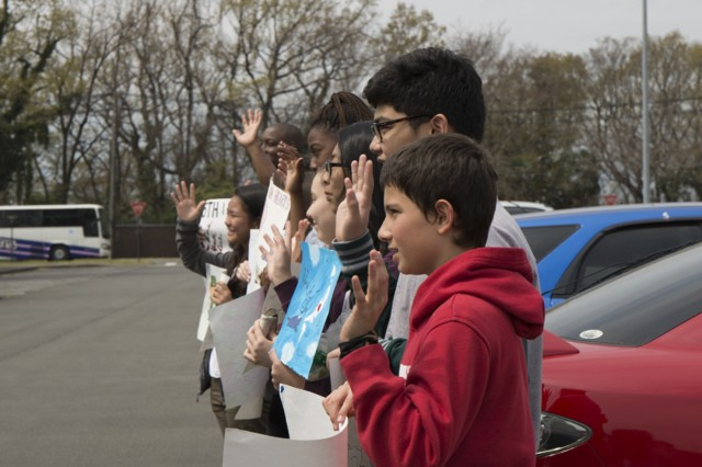 ZAMS school students wave goodbye Soldiers from 35th CSSB as they depart Camp Zama April 1 for training to the Combat Training Center at Fort Polk, La. (U.S. Army photo by Alia Naffouj)