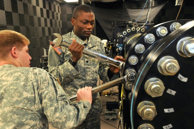 Spc. Daniel Oladejo (right) and Spc. Peter Johnson, biomedical science technicians with the U.S. Army Institute of Surgical Research, make adjustments to the shock tube Feb. 24 at Fort Sam Houston, Texas. The shock tube is a piece of equipment designed to simulate exposure to explosions similar to what Soldiers may encounter while in combat. The data collected from the device is crucial to the ocular research directorate, which focuses on research and advances in medicine aimed at helping Soldiers suffering from ocular related conditions.