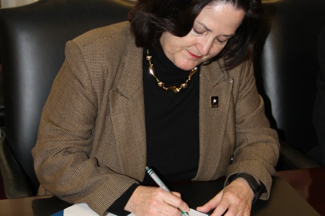 Katherine Hammack, the assistant secretary of the Army for installations, energy and environment signs a memorandum of agreement that formalizes the partnership between the service energy offices at the Pentagon, Washington, D.C., April 6, 2016.