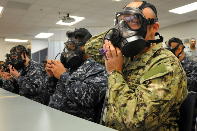 Coast Guard Reserve Lt. Douglas Dresnek, force protection and CBRN-E officer, Coast Guard Port Security Unit 312 out of San Francisco, California ensures his protection mask fits before stepping into the U.S Army Chemical, Biological, Radiological and Nuclear School, E.F. Bullene CBRN Defense Training Facility.