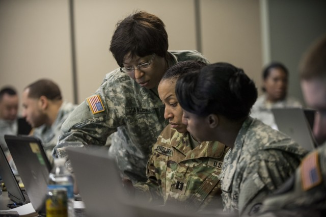 Sgt. 1st Class Sucrontay Stanley (left), works with Capt. Tahera English and Capt. DeMonica Nealy, all personnel officers and noncommissioned officers from different U.S. Army Reserve military police units, work together on updating personnel data for their units during a four-day workshop and Yearly Training Brief conference held by the 200th Military Police Command in Columbus, Ohio, on March 31. During the event, the units' leaders worked to improve their readiness and briefed the commanding general and his command leadership on their units' status. (U.S. Army photo by Master Sgt. Michel Sauret)