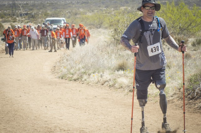 Former Navy Special Operations Master Chief Harold Bologna, of Virginia Beach, Va., walks ahead of retired U.S. Army Col. and Bataan Death March Survivor Ben Skardon and his entourage during the 27th annual Bataan Memorial Death March at White Sands Missile Range, N.M., March 20, 2016. Bologna lost his legs when he stepped on a land mine in Afghanistan in October, 2015 - just five months prior to this. Skardon, 98, is the only Bataan survivor that walks in the march. Both men walked more than eight miles.
