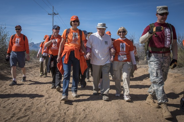 "Bataan Death March survivor and retired U.S. Army Col. Ben Skardon walks in the Bataan Memorial Death March at White Sands Missile Range, March 20, 2016. Skardon is the only survivor of the real march who walks in the memorial march. He is joined every year by ""Ben's Brigade"", a group of former students and supporters who wear the orange of his alma mater, Clemson University, where he was also a professor. (U.S. Army photo by Staff Sgt. Ken Scar)"