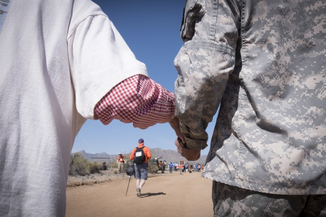 Reserve Officer Training Corps cadet Noah Cruse, a freshman studying industrial engineering at New Mexico State University (right) steadies retired U.S. Army Col. Ben Skardon, 98, as they walk in the 27th annual Bataan Memorial Death March, March 20, 2016. Skardon is the only Bataan survivor who walks in the march. (U.S. Army photo by Staff Sgt. Ken Scar)