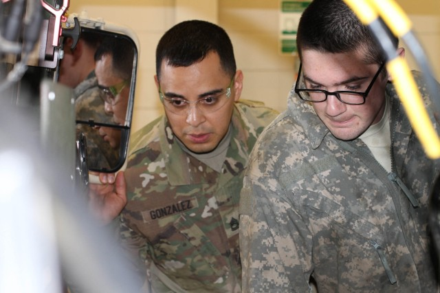 Course instructor Sgt. 1st Class Jorge Gonzalez provides guidance to Spc. Michael Sweat of the 411th Chemical Co., Edison, N.J, as he disassembles parts of a Humvee during the 80th Training Command's Wheeled Vehicle Mechanic Course at the Regional Training Site-Maintenance Fort Devens 31 March 2016.   The three-week course teaches students the basics of how to perform maintenance and repairs on four-wheeled military vehicles, primarily focusing on Humvees and Mine-Resistant Ambush Protected vehicles.