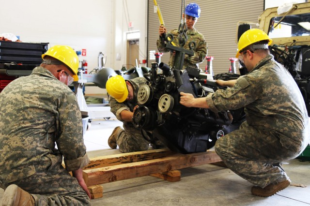 Course instructor Sgt. 1st Class Jorge Gonzalez provides guidance to students during the 80th Training Command's Wheeled Vehicle Mechanic Course at Regional Training Site-Maintenance, Ft. Devens, Mass., 30 March 2016, as they remove a Humvee's engine. The three-week course teaches students the basics of how to perform maintenance and repairs on four-wheeled military vehicles, primarily focusing on Humvees and Mine-Resistant Ambush Protected vehicles.