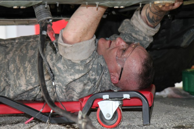 Sgt. Douglas Aho of the 110th Maintenance Co., Ft. Devens, Mass., re-connects the fuel supply line underneath a Humvee as he and his fellow students reassemble the vehicle. The students took the Humee engine apart during their final training task while attending the first phase of the 80th Training Command's Wheeled Vehicle Mechanic Course at the Regional Training Site-Maintenance Fort Devens, 31 March 2016. The three-week course teaches students the basics of how to perform maintenance and repairs on four-wheeled military vehicles, primarily Humvees and Mine-Resistant Ambush Protected vehicles.