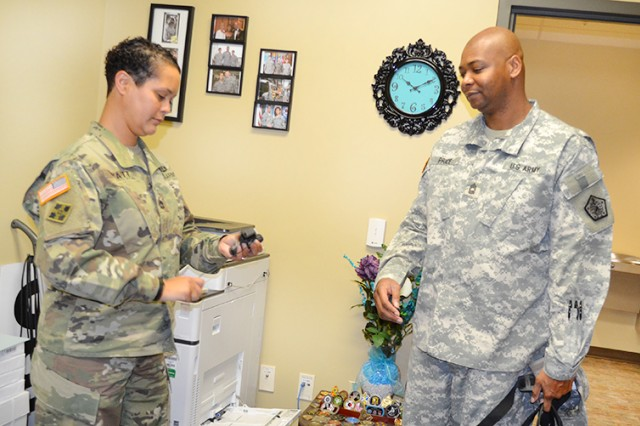 Sgt. 1st Class Shannon Wyatt, Sexual Harassment/Assault Response and Prevention, or SHARP, program manager with U.S. Army Human Resources Command, hands off an emergency contact phone to victim advocate, Master Sgt. Antonia Price, in her office at the Maude Complex on Fort Knox, Kentucky, April 8, 2016. Price, Reserve NCOIC with HRC's Special Management Division, Officer Personnel Management Directorate, is one of 22 HRC Soldiers presently volunteering as advocates, pledged to come to the aid of victims of rape and assault any time of day or night, 365 days a year.