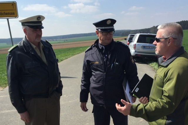 Ernest Roth (right), 7th Army Joint Multinational Training Command maneuver liaison officer, works with German officials during the Saber Junction 16 rehearsal, April 11, to ensure a safe and successful airborne jump and tactical movement in maneuver rights area near Hohenfels, Germany.