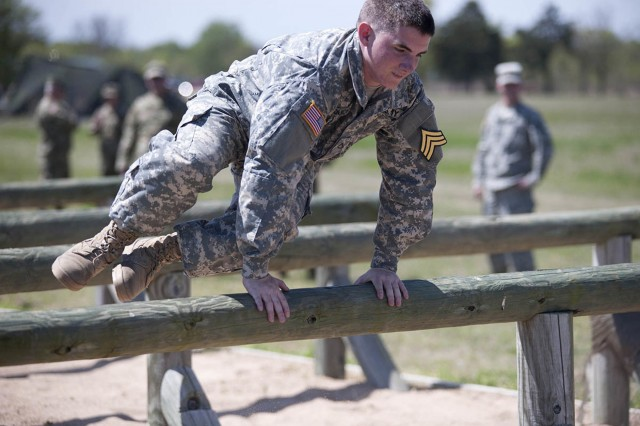 Pfc. Arron Couch, bounds over wooden obstacles while competing in the Oklahoma Army National Guard Recruit Sustainment Program's Warrior Challenge at Camp Gruber Training Center in Braggs, Oklahoma, April 9. The competition prepares newly-enlisted Soldiers for basic combat training, foster esprit de corps, build teamwork and educate participants on the equipment and capabilities of the Oklahoma Army National Guard.