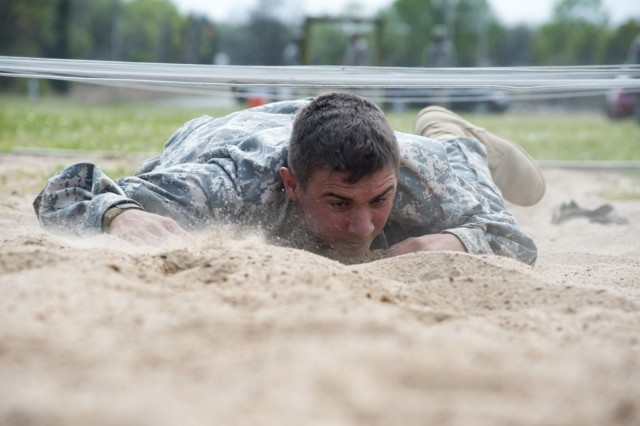 Pvt. William Elmore, low-crawls through an obstacle during the Oklahoma Army National Guard Recruit Sustainment Program's Warrior Challenge at Camp Gruber Training Center in Braggs, Okla., April 9. The competition prepares newly-enlisted Soldiers for basic combat training, foster esprit de corps, build teamwork and educate participants on the equipment and capabilities of the Oklahoma Army National Guard.