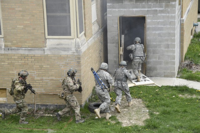 Soldiers and Airmen from the Indiana National Guard move into a building at Muscatatuck Urban Training Center during the Bold Quest 16.1 Distinguished Visitors Day, April 6.