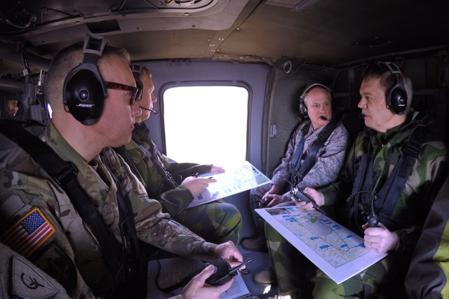 Indiana National Guard Assistant Adjutant General Brig. Gen. John McGoff (right, nearest window) speaks with Lt. Gen. Ander Silwer, Chief of Swedish Armed Forces Training and Development, as they circle the Atterbury-Muscatatuck Complex in a UH-60 Blackhawk helicopter during the Bold Quest 16.1 Distinguished Visitors Day on Wednesday, April 6. (Indiana National Guard photo by Master Sgt. Brad Staggs, Atterbury-Muscatatuck Public Affairs)