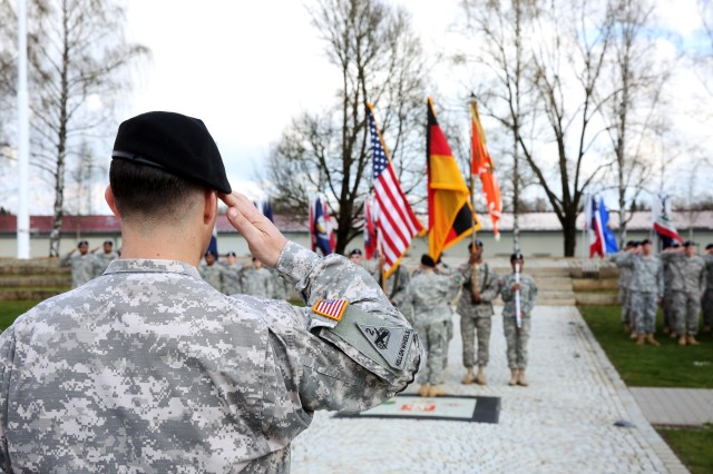 Command Sgt. Maj. Woody Carter, 52nd Signal Battalion outgoing senior enlisted advisor, salutes during the playing of the national anthem at the 52nd Signal Battalion change of responsibility ceremony April 7, 2016 at Patch Barracks in Stuttgart.