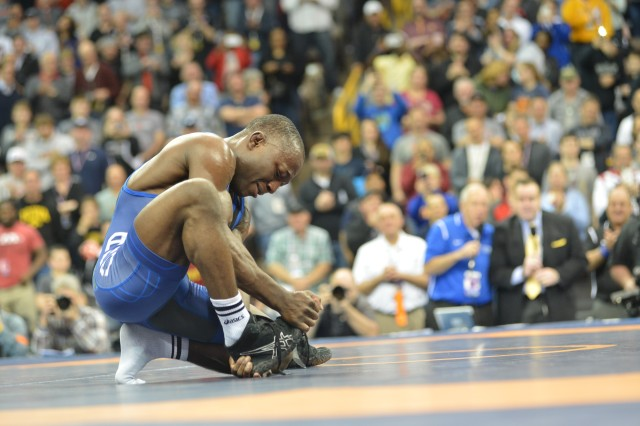 Two-time Olympian Sgt. Spenser Mango of the U.S. Army World Class Athlete Program removes his shoes and leaves them on the mat, a wrestler's way of signaling retirement from competition in the sport, during the 2016 U.S. Olympic Wrestling Team Trials on April 9 at Carver-Hawkeye Arena on the campus of the University of Iowa in Iowa City. (U.S. Army photo by Tim Hipps)