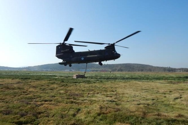 A Greece Air Force Chinook cargo helicopter begins to lift a Type Five Palette System that riggers from 5th Quartermaster Theater Aerial Delivery Company and Greece's 865th Aerial Delivery Battalion hooked onto it, April 5, at the Greek Air Force Base in Elefsis, Greece.
