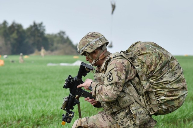 A U.S. Army Paratrooper with the 173rd Airborne Brigade unpacks his weapon during large scale airborne operations as part of Exercise Saber Junction 16 on the Maneuver Rights Area near Hohenfels, Germany, April 12, 2016. Over 1000 paratroopers and multiple Container Delivery Systems bundles were deployed to provide initial logistical support for follow on missions. Saber Junction 16 will evaluate and assess the readiness of the U.S. Army's 173rd Airborne Brigade to conduct land operations in a joint, combined environment and to promote interoperability with participating Allied and partner nations. Countries participating in the exercise include Albania, Armenia, Bosnia and Herzegovina, Bulgaria, Hungary, Italy, Latvia, Lithuania, Macedonia, Moldova, Romania, Serbia, Slovenia, Sweden, the United Kingdom and the United States. (U.S. Army photo by Visual Information Specialist Gertrud Zach/released)