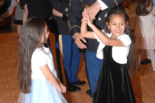 Sgt. 1st Class Robert Villarreal dances with his daughters, Leah, 6, and Melanie, 5, at the annual Fort Leonard Wood Father Daughter Ball Friday at Nutter Field House.