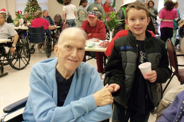 Cavan McIntyre-Brewer, now 14, poses with Korean War veteran Wade Holder. Holder inspired Cavan's organization, Socks for Vets, when they met during a Cub Scout trip to the hospital and Cavan realized Holder didn't have any socks. He's since helped almost 10,000 veterans. Cavan also raises and trains pack goats to assist wounded warriors who enjoy nature and like to hike and gives out backpacks full of nonperishable food and necessities to homeless veterans. He was honored by Operation Homefront as the 2015 Military Child of the Year for the Army. His sister, Lorelie, 10, was born with half a heart and received the honor this year in recognition of her work to help other pediatric cardiology patients. (Photo courtesy of Chelle McIntyre-Brewer)