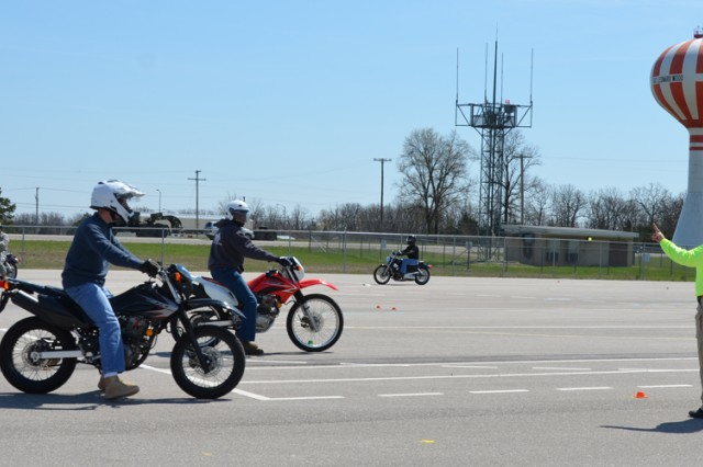 Tami Grieder, Army Traffic Safety Program motorcycle instructor, observes students practicing proper stopping techniques during Fort Leonard Wood's two-day Basic Rider Course. The course is mandatory for all service members wanting to ride on post.