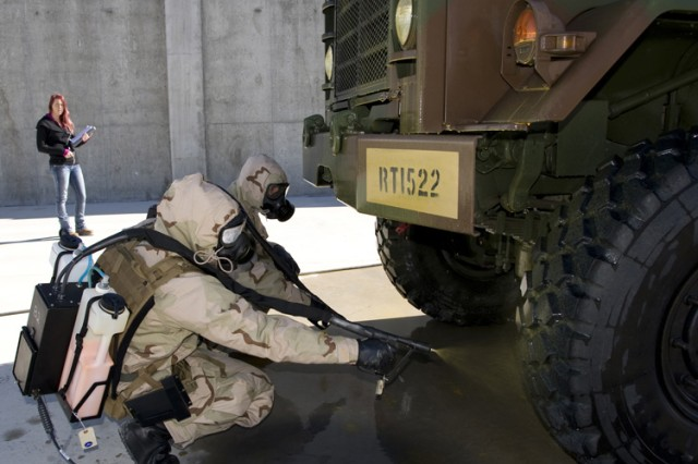 Spc. Brittany Mattison (foreground) sprays indicator solution to the underside of a truck during Contamination Indicator Decontamination Assurance System (CIDAS) testing April 7, 2016 at Dugway Proving Ground, Utah. Beside her is Spc. Taylor Wood. Both Soldiers are from the 690th Chemical Company of the Alabama National Guard, sent to Dugway for the test. Data Collector Elisa Saurette, in the background, takes meticulous notes for the later test report. (Photo by Al Vogel / Dugway Public Affairs)