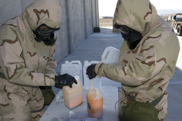 Spc. Taylor Wood and Spc. Brittany Mattison mix Agentase powder with water during the Contamination Indicator Decontamination Assurance System (CIDAS) test April 7, 2016. The indicator solution was used in prototype backpack-mounted applicators. The Soldiers, from the 690th Chemical Company of the Alabama National Guard, were sent to Dugway Proving Ground, Utah, for CIDAS testing. (Photo by Al Vogel / Dugway Public Affairs)