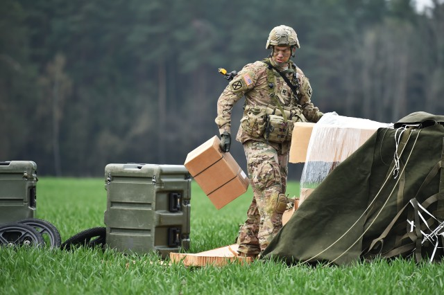 A U.S. Army Paratrooper with the 173rd Airborne Brigade unpacks dropped cargo during large scale airborne operations as part of Exercise Saber Junction 16 on the Maneuver Rights Area near Hohenfels, Germany, April 12, 2016.