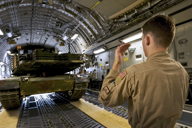 Airman 1st Class Kenneth Whitler, a 7th Airlift Squadron aircraft loadmaster from Joint Base Lewis-McChord, Washington, directs an M1A2 Abrams main battle tank onto a C-17 Globemaster III aircraft at Ramstein Air Base, Germany. Airmen and Soldiers from across the U.S. European Command theater worked together to transport two tanks to Bulgaria to participate in multinational training in support of Operation Atlantic Resolve.