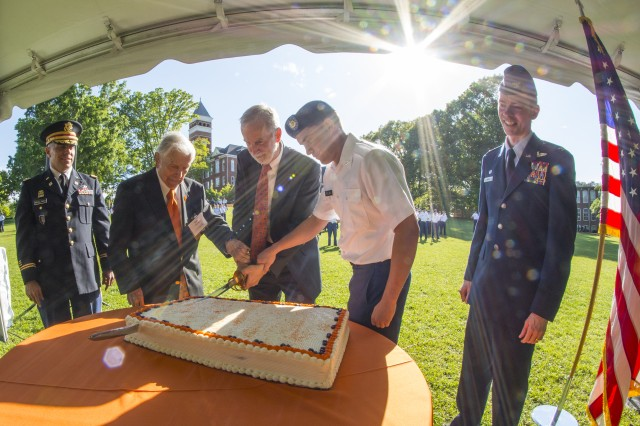 Clemson University Provost Bob Jones (center), retired U.S. Army Col. Ben Skardon (second from left), and Reserve Officers' Training Corps cadet Zackary Ballard cut the cake during the ROTC 100th anniversary celebration on Bowman Field, April 14, 2106. Skardon is 98 and Ballard is 18. (Photo by Ken Scar)