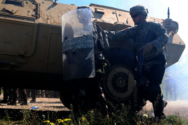Soldiers from the 1st Battalion, 41st Infantry Regiment, 2nd Infantry Brigade Combat Team, operating as members of the Multinational Battle Group-East, take cover behind a riot control vehicle, April 16, during Operation Stalwart Strike at Camp Marechal De Lattre De Tassigny. Kosovo, During the operation the U.S. Soldiers partnered with multinational elements from Kosovo Force during a crowd riot control scenario.