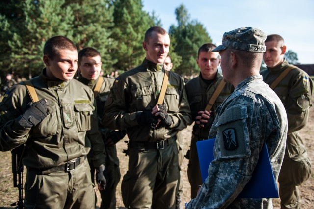 U.S. Army Spc. Zhabka Aleksey, a California National Guard Soldier from the 223rd Military Intelligence Battalion talks to a group of Ukrainian National Guard Soldiers during situational training exercise lanes at Exercise Rapid Trident in 2014 in Yavoriv, Ukraine. Rapid Trident is an annual U.S. Army Europe conducted, Ukrainian led, multinational exercise designed to enhance interoperability with allied and partner nations while promoting regional stability and security.