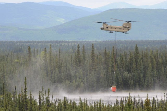 A CH-47 Chinook from Bravo Company, 1st Battalion, 52nd Aviation Regiment fills a 'Bambi Bucket' with 1400 gallons of water, Jul. 9, 2013 at Fort Wainwright, Alaska.  The unit is supporting the Alaska Fire Service's fight against the Stuart Creek 2 wildfire.