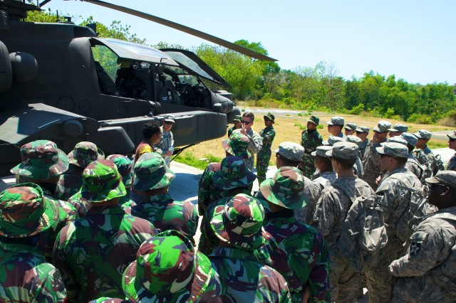 Members of Indonesia's 411th Raider Infantry Battalion join Soldiers of the 2nd Battalion, 1st Infantry, 2nd Stryker Brigade Combat Team, 2nd Infantry Division, for an AH-64 Apache familiarization brief by Chief Warrant Officer 2 Jake Uber, of the 25th Combat Aviation Brigade, during Exercise Garuda Shield, in Indonesia, Sept. 25, 2014.  The exercise was part of Pacific Pathways.