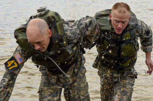U.S. Army Capt. Robert Killian helps Staff Sgt. Erich Friedlein, National Guard Rangers, exit Victory Pond after  swimming toward the next event at Fort Benning, Ga., April 15, 2016. The 33rd annual Best Ranger Competition 2016 is a three-day event consisting of challenges to test competitor's physical, mental, and technical capabilities.