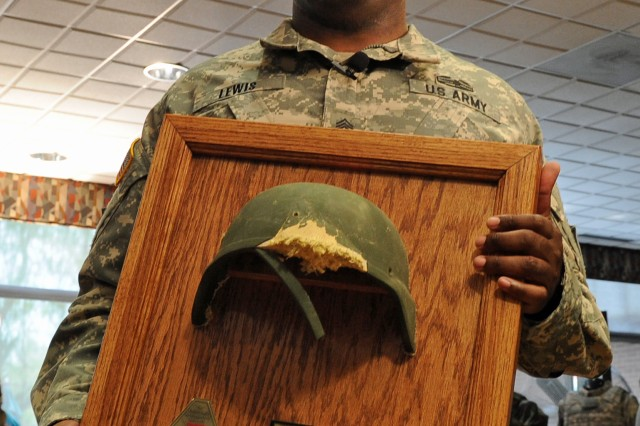 Staff Sgt. Thalamus Lewis displays the Army Combat Helmet he was wearing when he was shot while searching for hidden explosives in Afghanistan Oct. 4, 2012. The helmet was returned to him in a ceremony hosted by Program Executive Office Soldier at Fort Belvoir, Va., April 20, 2016.