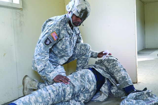 Staff Sgt. Clark Burns Jr., an NCO competitor from the Quartermaster School, checks a medical dummy for injury at the first-aid testing station during CASCOM Ultimate Warrior competition.