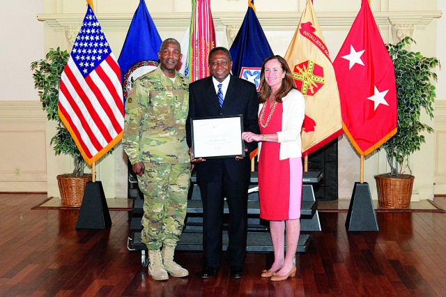 First lady of Virginia Dorothy McAuliffe and Maj. Gen. Darrell K. Williams, CASCOM and Fort Lee commanding general, present a Lifetime Achievement Award to retired Army veteran Rufus Montgomery.
