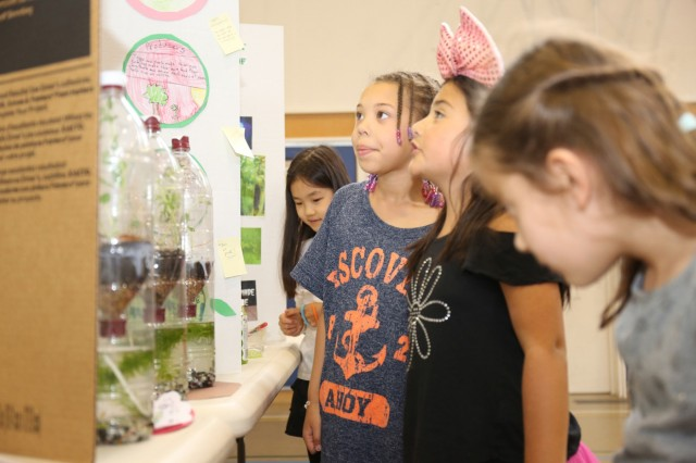 Arnn students look at the 3rd-grade class science project of an ecosystem during the annual school's science fair held April 21 inside the school's gymnasium. (U.S. Army photo by Noriko Kudo)