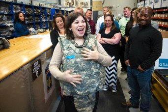 Lauren Aggen, equal employment specialist, U.S. Army Sustainment Command, tries on body armor during a tour of a Central Issuance Facility at Fort Bragg, North Carolina, April 7. (Photo by Kevin Fleming, ASC Public Affairs)