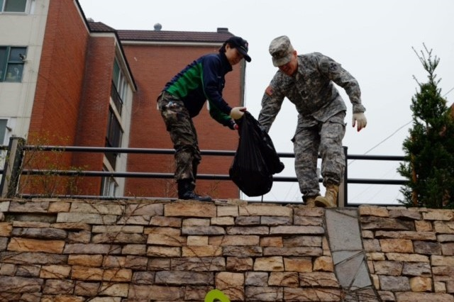 A Soldier from the 2501st Detachment Liaison Detachment and a cadet from Yongin University ROTC pick up trash near the Yongin River on Saturday, Apr. 9 during an area beautification project.