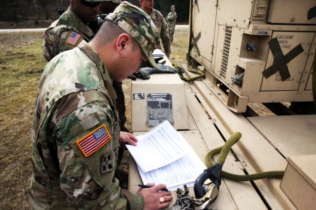 Sgt. Angelo Cruz, sling load inspector from the Regimental Support Squadron, 2nd Cavalry Regiment, inspects the load plan paperwork prior to sling load operations with the 44th Expeditionary Signal Battalion March 22, 2016 at the Grafenwoehr Training Area, Germany. (U.S. Army photo by William B. King)