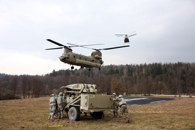 Soldiers from the 44th Expeditionary Signal Battalion, 2nd Signal Brigade move a Satellite Transportable Terminal into position to be sling loaded by a CH-47 Chinook helicopter from the 12th Combat Aviation Brigade during sling load and air operations training March 22, 2016 at the Grafenwoehr Training Area, Germany. (U.S. Army photo by William B. King)